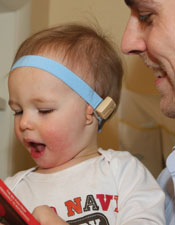 Young child on parent's lap wearing a Baha bone conduction hearing aid