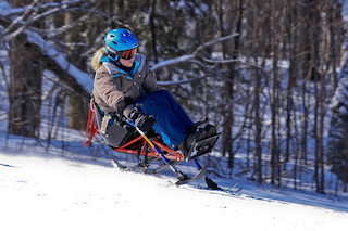 Skier using Adaptive Skiing equipment with Outriggers